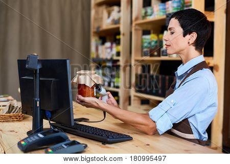 Shop assistant scanning jar with pickled vegs