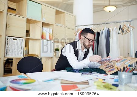 Modern tailor choosing fabric samples for new clothes collection