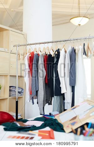 Clothes on rail and desks with fabric samples near by