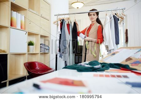 Young fashion designer looking through clothes on rail