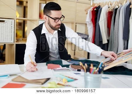 Couturier choosing samples of fashionable fabric for new collection