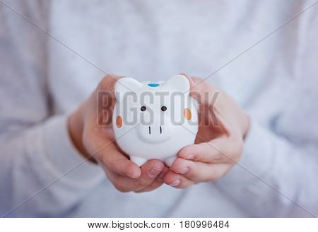 Closeup hild hands holding a money box or piggy bank. Business fund.