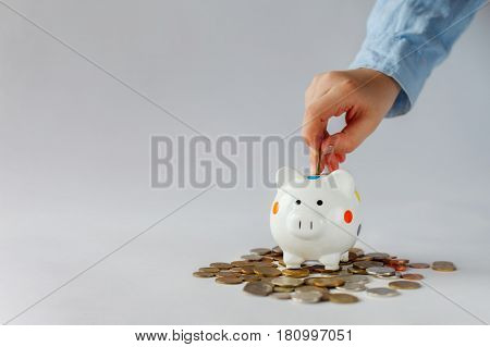 Kid hand putting coin into piggy bank or money box. Save concept.