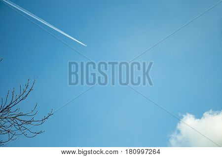 Condensation track of an airplane in a blue sky with clouds