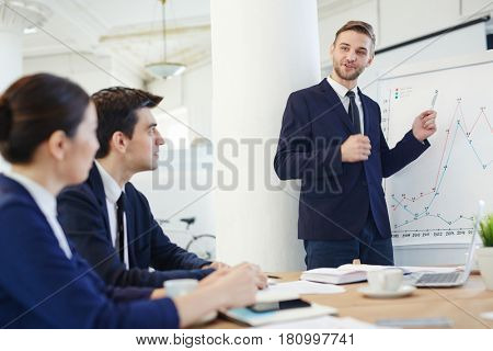 Young confident man pointing at whiteboard while explaining graph