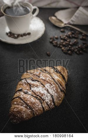 Traditional french breakfast croissant with chocolate and coffee on black stone table