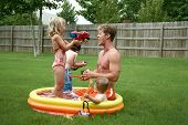 Boys and Girl with Dad in the kiddie pool. poster