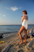 slavonic bride in body and sunglasses smokin on seashore poster