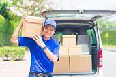 Delivery concept - Smiling happy young asian handsome male postal delivery courier man in front of cargo van delivering package carrying box with service mind and blue uniform poster