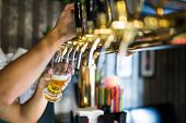 barman hand at beer tap pouring draught lager beer serving in a restaurant or pub. poster
