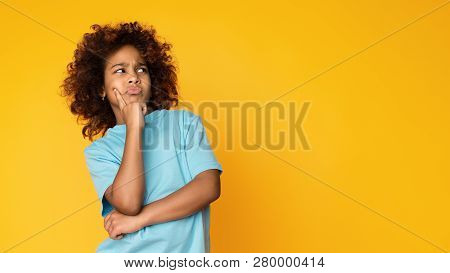 Let Me Think. Doubtful, Thoughtful Child Girl Posing Over Yellow Background, Copy Space