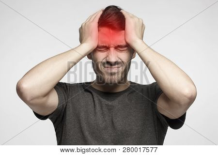 Young Man Isolated On Gray Background, Showing How Much Head Hurts, Experiencing Pain, Looking Miser
