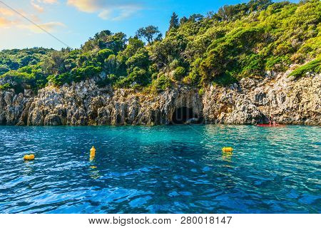 Corfu, Greece - September 16 2018: Two Young Women Paddle Board Past The Blue Cave On The Coast Of T