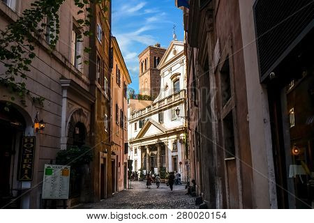 Rome, Italy - September 30 2018: Tourists Walk Past Shops Down A Shaded Back Alley Towards The Saint
