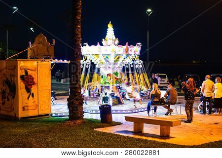 Brindisi, Italy - September 20 2018: Parents Watch Children Enjoy A Carousel Ride In The Evening At