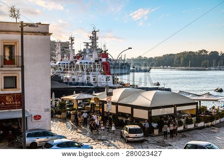 Brindisi, Italy - September 23 2018: An Italian Family Waits Outside A Waterfront Restaurant Near Na