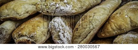 A Stack Of Fresh Bread Sitting On A Table At An Outdoor Market.