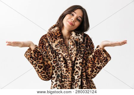 Portrait of a pretty brunette woman dressed in leopard coat shrugging shoulders isolated over white background