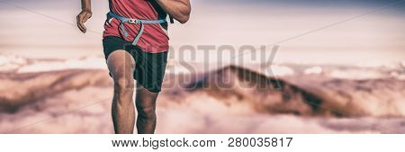 Trail run runner man athlete training on difficult path climbing up mountain top reaching summit. Endurance sport active lifesytle banner panorama.
