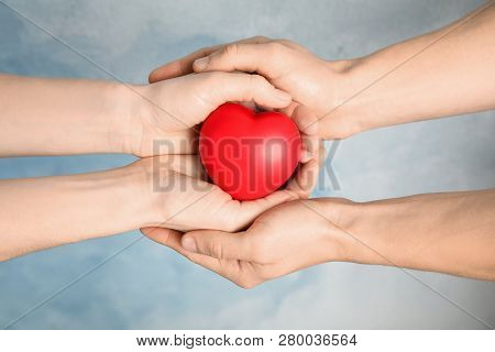 People Holding Red Heart Against Color Background, Closeup. Cardiology Concept