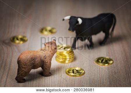 Cryptocurrency bitcoin bear and bull figures on a wooden table. Bearish or bullish market trend concept poster