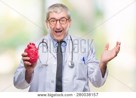 Handsome senior cardiologist doctor man holding heart over isolated background very happy and excited, winner expression celebrating victory screaming with big smile and raised hands