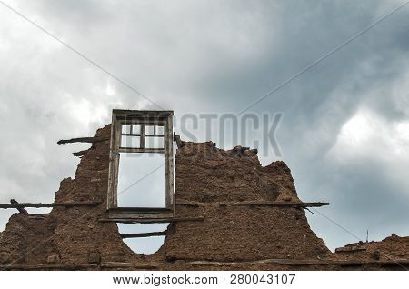 Brick wall with adobe clay plaster and broken wooden window frame remained of ruined old rural country house on cloudy blue sky background poster
