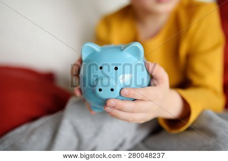 Little Boy Shaking A Piggy Moneybox And Dreams Of What He Can Buy. Education Of Children In Financia
