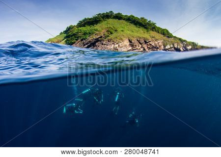 Scuba divers underwater beside tropical island in Thailand