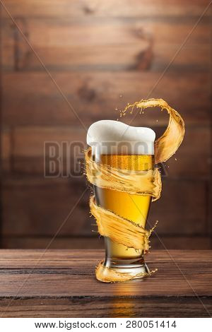 A glass of cold beer with drops and froth around a splash on a dark wooden background with copy space. poster