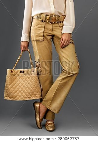 Elegant woman wearing  silk  blouse  and golden trousers on grey.