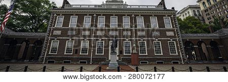 The Front Of Independence Hall In Philadelphia, Pa On A Cloudy Summer Day With The American Flag At
