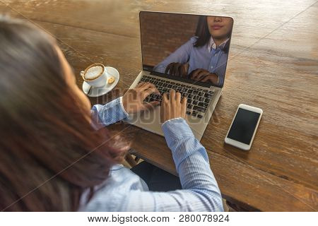 Young Woman Working On Laptop With Smartphone And Hot Cup Of Cappuccino In The Table