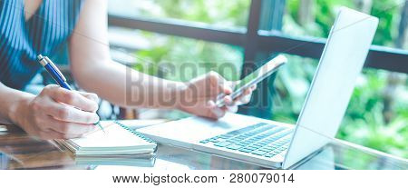 Business Woman Hand Is Writing On A Notepad With A Pen And Using A Mobile Phone.