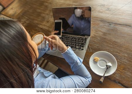 Top View Of Asian Office Woman Drinking Hot Coffee And Using Smartphone In The Office