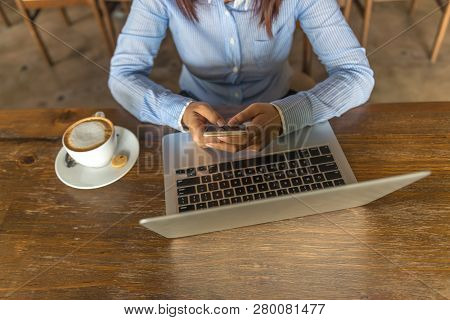 Young Businesswoman In Shirt Using Smartphone In The Cafe