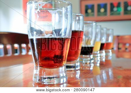 A Closeup Look At A Row Of Beer Samples On A Table In A Tasting Room.