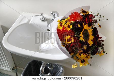 A Flower Boquet Lays On Its Side In A White Sink.