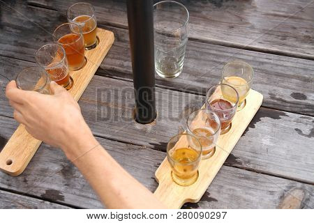Male Hand Reaching Across A Picnic Table To Grab A Beer Sample From A Selection Of Samples On A Padd