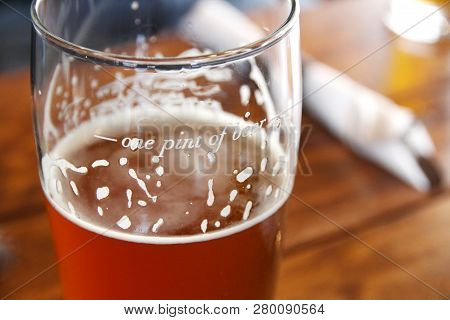 Closeup Of Beer In A Pint Glass On A Table.  The Glass Is Marked With The Measurement For