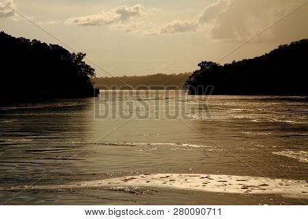 River Shoreline Silhouette Seen From The Middle Of A River As You Are About To Pass Between Two Peni