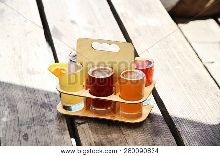 Six Different Beer Samples In A Wooden Sampler Holder Sitting On A Picnic Table In Bright Sunshine.