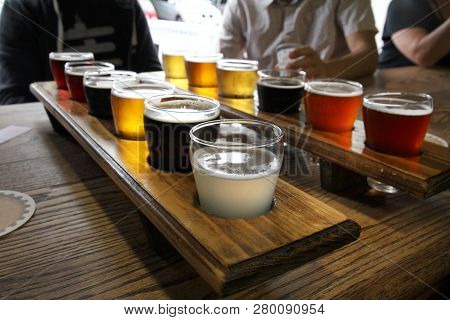 Twelve Beer Samples Being Shared At A Table By Some Men.