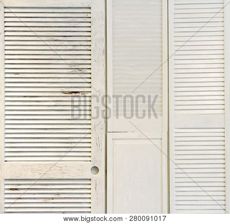 White Wooden Shutters From Windows And Doors Attached To A Wall As Panelling.