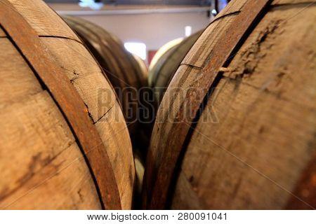 Looking Between The Rows Of Wooden Liquor Barrels.