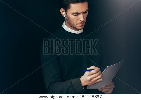 Portrait Of Pensive Young Handsome Man Have A Conversation With Colleagues During Meeting With Wirel