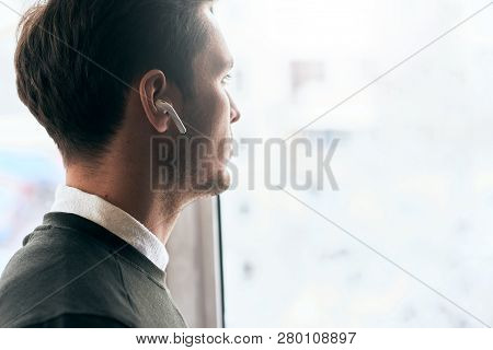 Horizontal Image Of Young Handsome Man Have A Call With A Friend And Looking Through The Window In O