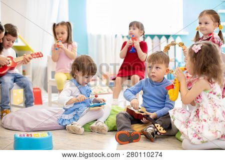 Group Of Smart Kids Age 3-4 Years Playing Diverse Musical Toys. Early Musical Education In Kindergar