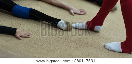 Legs Of Young Girls Woman At The Gym Doing Split Exercise. Row Of Female Legs Couple Of Girls Sittin