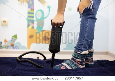 Woman With Hand Air Pump Inflatable Mattress Or Inflatable Bed At Home. Body Part, Selective Focus